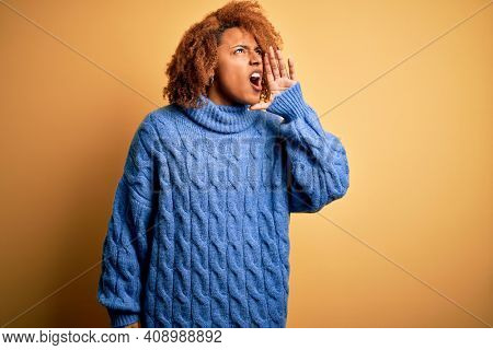Young beautiful African American afro woman with curly hair wearing blue turtleneck sweater shouting and screaming loud to side with hand on mouth. Communication concept.