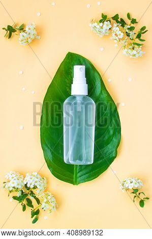Hand Sanitizer On The Oval Leaf On The Frame Of Spirea Flowers. Light Yellow Background. Hand Saniti