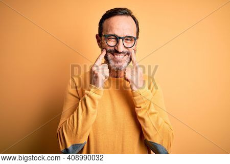 Middle age hoary man wearing casual sweater and glasses over isolated yellow background Smiling with open mouth, fingers pointing and forcing cheerful smile