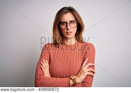 Young beautiful brunette woman wearing casual sweater and glasses over white background skeptic and nervous, disapproving expression on face with crossed arms. Negative person.