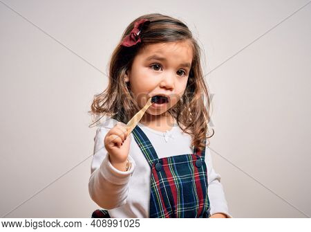 Young little infant girl brushing her teeth using tooth brush and oral paste, cleaning teeth and tongue as healthy health care morning routine. Learning dental education
