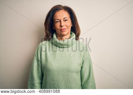 Middle age beautiful woman wearing casual turtleneck sweater over isolated white background Relaxed with serious expression on face. Simple and natural looking at the camera.