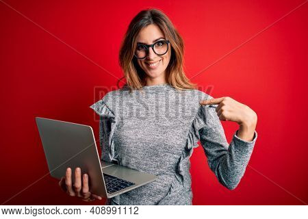 Young beautiful brunette businesswoman wearing glasses using laptop over red background with surprise face pointing finger to himself