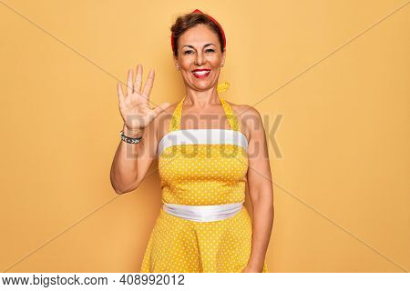 Middle age senior pin up woman wearing 50s style retro dress over yellow background showing and pointing up with fingers number five while smiling confident and happy.