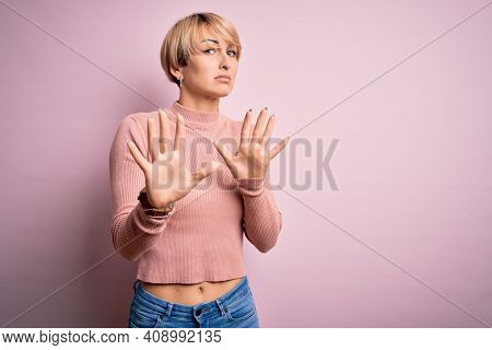 Young blonde woman with short hair wearing casual turtleneck sweater over pink background Moving away hands palms showing refusal and denial with afraid and disgusting expression. Stop and forbidden.