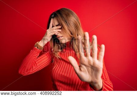 Young beautiful brunette woman wearing casual turtleneck sweater over red background covering eyes with hands and doing stop gesture with sad and fear expression. Embarrassed and negative concept.