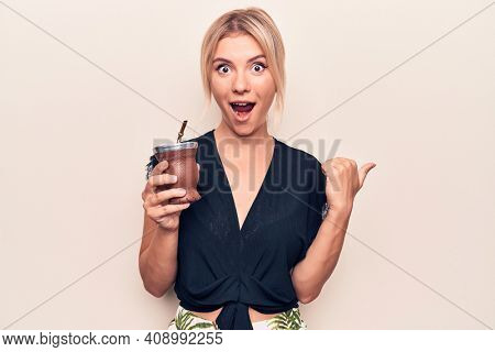 Young beautiful blonde woman drinking cup of mate infusion beverage over white background pointing thumb up to the side smiling happy with open mouth