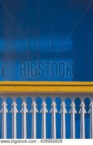 Sunlight And Shadow On Surface Of White Balustrade On Terrace In Front Of Blue Wooden Door In Vintag