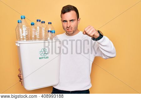 Young handsome man with blue eyes recycling holding wastebasket with plastic bottles annoyed and frustrated shouting with anger, yelling crazy with anger and hand raised