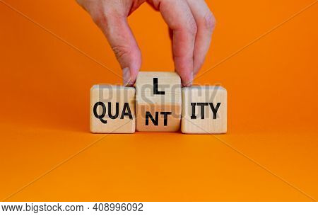 Quality Over Quantity Symbol. Businessman Turns Cubes And Changes The Word 'quantity' To 'quality'.