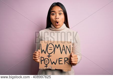 Young asian activist girl asking for women rights holding banner with woman power message scared in shock with a surprise face, afraid and excited with fear expression