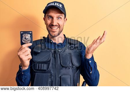 Young handsome policeman wearing uniform and bulletprof holding police badge celebrating achievement with happy smile and winner expression with raised hand