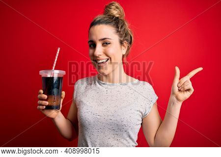 Beautiful blonde woman drinking cola fizzy beverage to refreshment over red background very happy pointing with hand and finger to the side