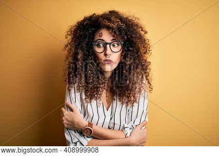 Young beautiful woman with curly hair and piercing wearing striped shirt and glasses shaking and freezing for winter cold with sad and shock expression on face