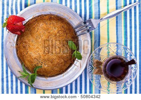 Turkish dessert kunefe isolated on a picnic cloth with mints and sliced strawberry along with Turkish hot tea poster