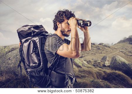 young explorer in high mountain looks horizon with binoculars