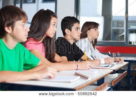 Side view of teenage students looking away while studying at desk in classroom