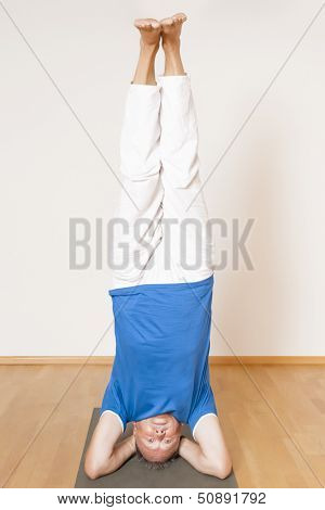 An image of a man doing yoga exercises - Salamba Shirshasana Head Stand
