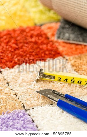Colorful carpet swatches, tape measure and  boxcutter