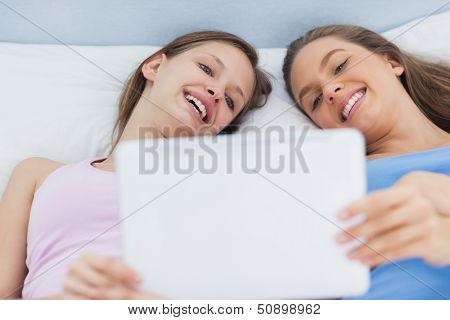 Happy girls lying in bed holding tablet and smiling at sleepover