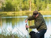 Fisherman get a perch with rod and reel horizon image poster