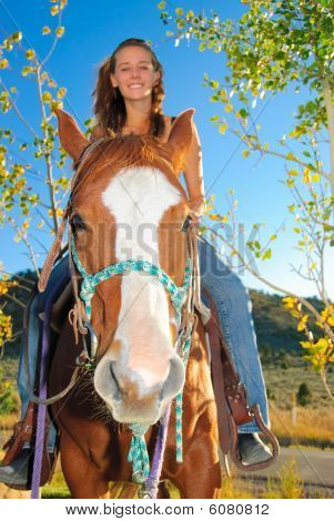 Teen on a horse outside on sunny afternoon. poster