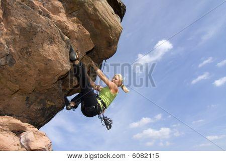 Young Woman Climbing A Rock