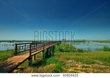 Wooden Bridge In To The Lake And Blue Sky
