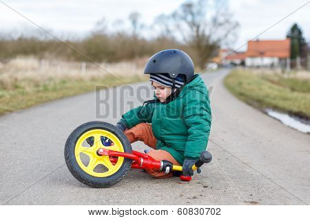 Adorable Little Toddler Boy Sad About His Broken Bicycle, Sitting Outdoors On The Street.
