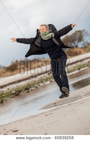 Happy Senior Woman Frolicking On The Beach