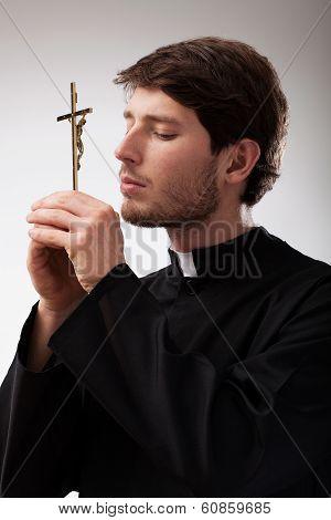 Priest Praying To Cross