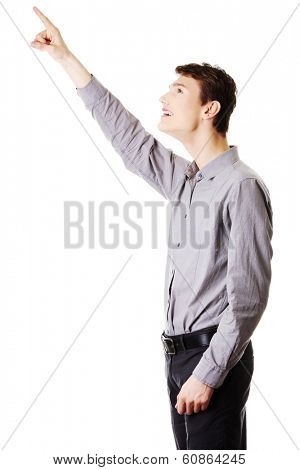 Portrait of young happy businessman pointing up with his finger
