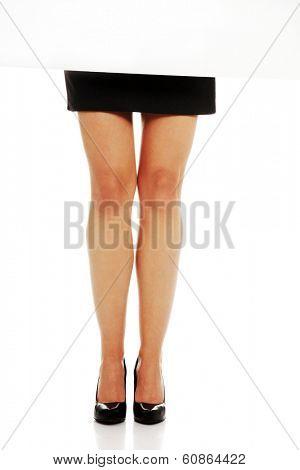 Beautiful slim businesswoman legs in elegant shoues and skirt behind blank board