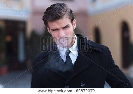 closeup portrait of an elegant young business man, outdoor, exhaling smoke while looking into the camera
