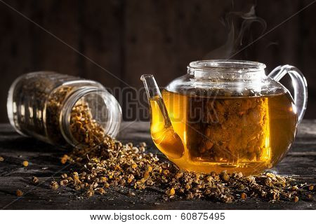 Hot Chamomile Tea In A Clear Teapot And Dried Flowers