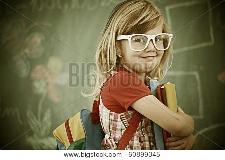 Cheerful colorized retro fashion little girl at school room having education activity
