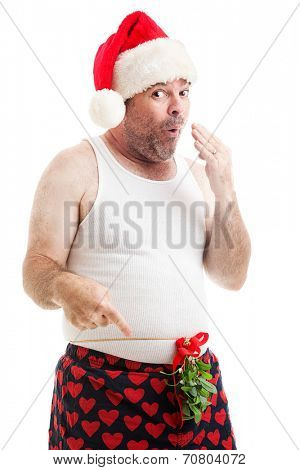 Scruffy looking man in his underwear with Christmas Mistletoe tied around his waist, looking naughty.  Isolated on white.