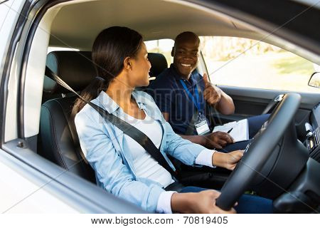 smiling driving instructor giving thumbs up to learner driver during test