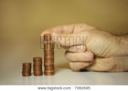 Hands Of Male Stacking Cents And Pennies To Save Money