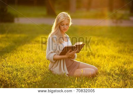 Girl Sitting On The Grass And Reading A Book