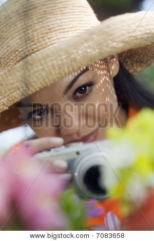 Young Woman Taking Pictures Of Flowers