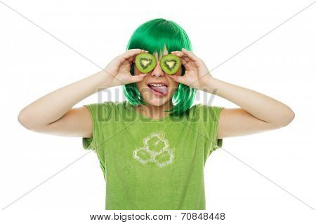 Cute young girl in a green wig and t-shirt holding two slices of green kiwifruit to her eyes as she playfully sticks out her tongue, on white