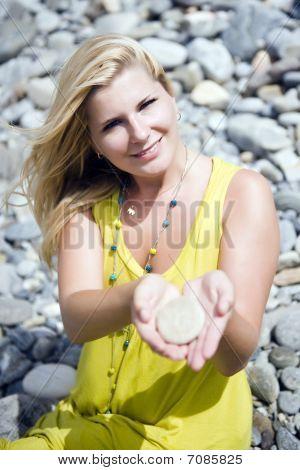 Unga vackra kvinnan i sten Zen Garden håller några stenar i händerna