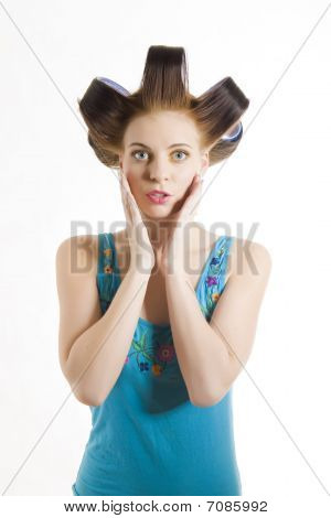 Young Beautiful Surprized Woman In Blue Shirt With Curlers On Her Hair . Isolated On White Backgroun