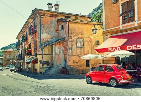 TENDE, FRANCE - AUGUST 12, 2014: Red Volkswagen beetle on the street of Tende - small town in French Alps popular with tourists and known for its cheese, honey and jams.