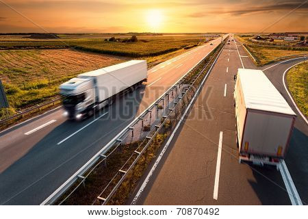 Two Trucks On Highway In Motion Blur