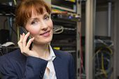Pretty computer technician talking on phone beside open server in large data center poster