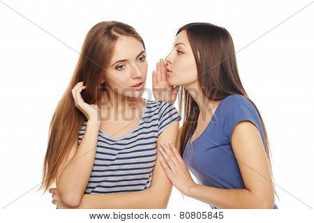 Two smiling girls friends whispering