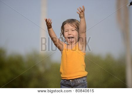 little toddler girl playing and dancing in the summer rain