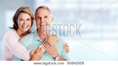 Happy senior loving couple over blue background